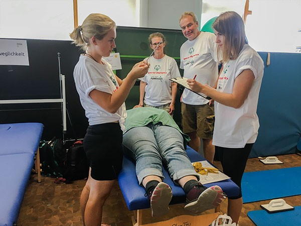 Therapeuten bei der Untersuchung eines Menschen mit geistiger Behinderung auf einer mobilen Massageliegen von Clap Tzu